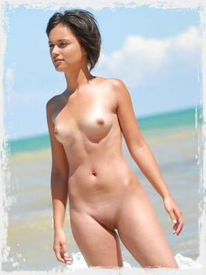 Nice angel poses nude in waves on a beach.